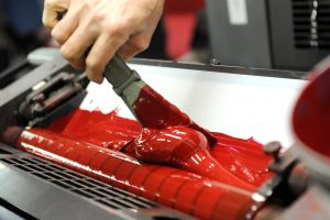Worker uses specialized spatula to apply red paint to industrial printer | Marsid-M&M Group
